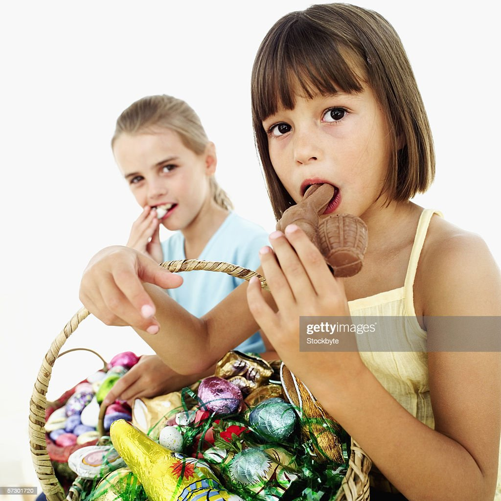 portrait of two girls eating chocolate easter bunnies from a