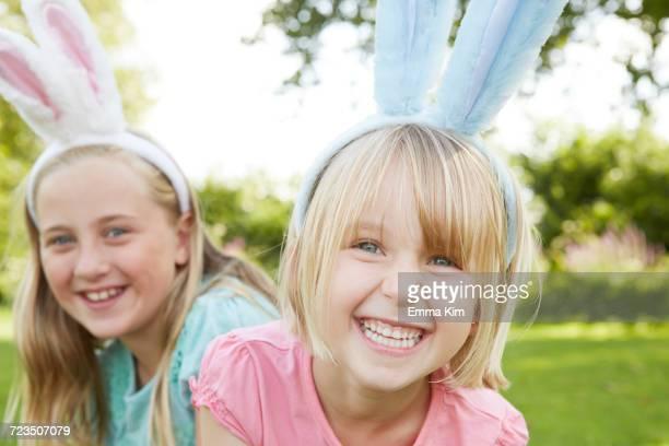 Portrait of two girls in feather headdress in garden