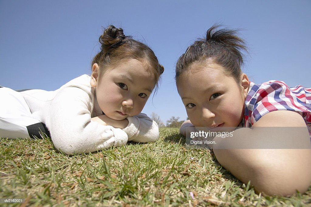 Portrait of Two Girls Lying in the Grass : Stock Photo
