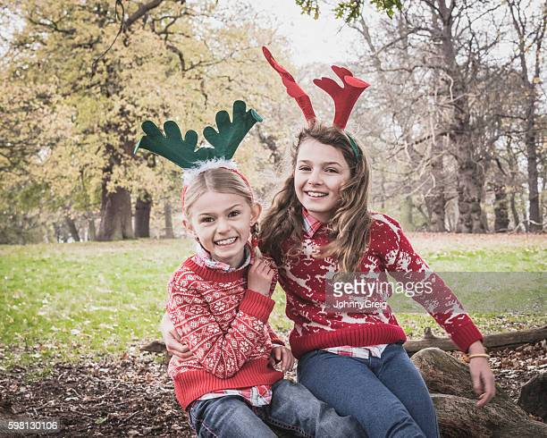 Portrait of two girls wearing antlers, arms around each other
