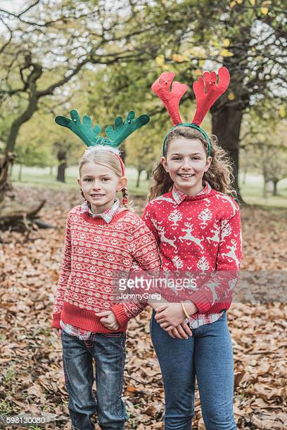 Portrait of two girls wearing Christmas jumpers and reindeer antlers