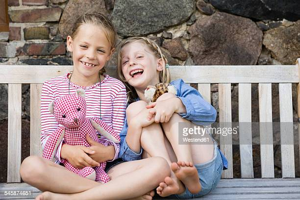 Portrait of two happy girls sitting on a bench with their soft toys