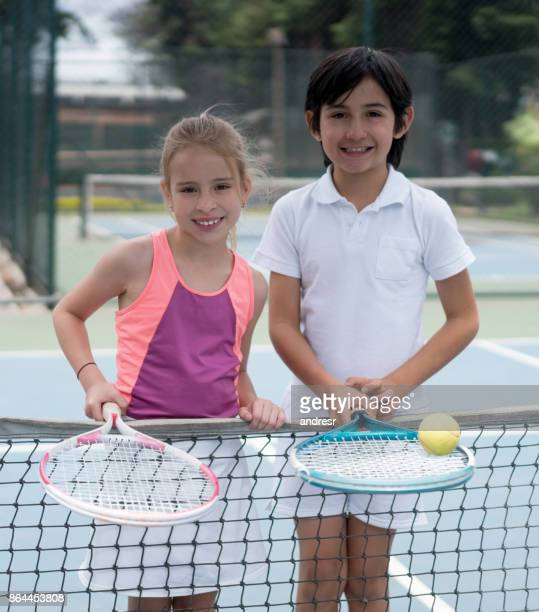 Portrait of two happy kids playing tennis