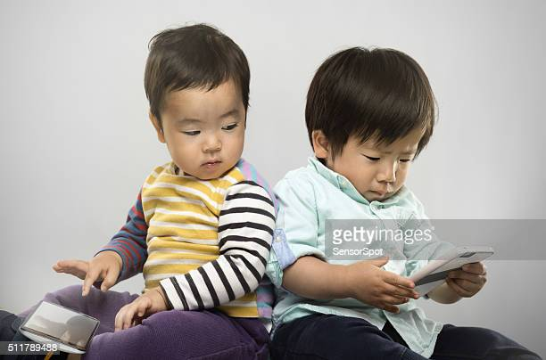 Portrait of two japanese kids with their electronic devices.