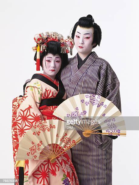 Portrait of two Kabuki actors, one acting as female, holding fans, Front View