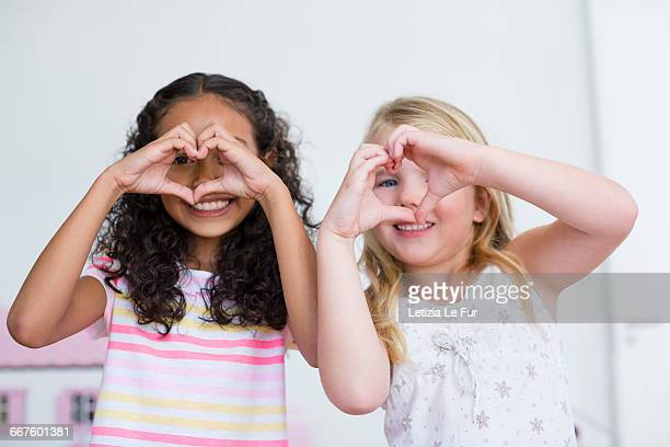 Portrait of two little girls making heart shape with hands