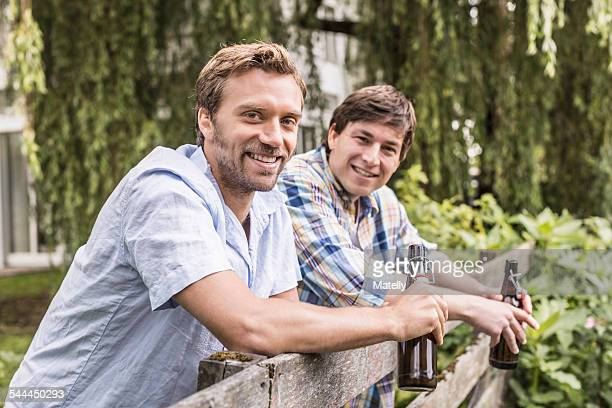 Portrait of two male adult friends leaning on garden fence drinking beer