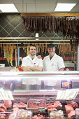Portrait of two male butchers in shop