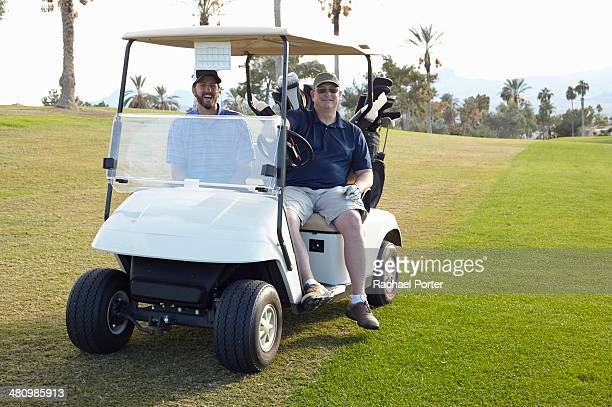 Portrait of two male golfers in golf buggy