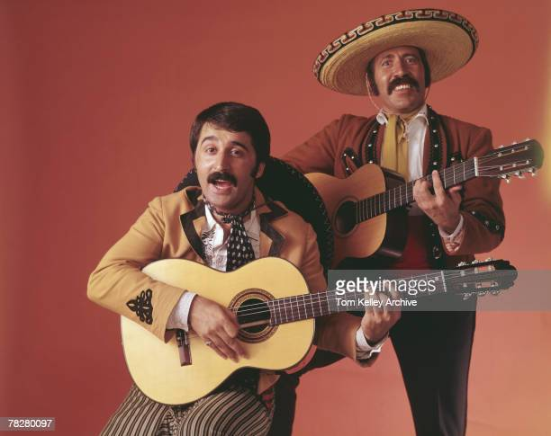 Portrait of two male models dressed as mariachis in short bolerostyle jackets and somberos similar to traditional charro suits as they play acoustic...