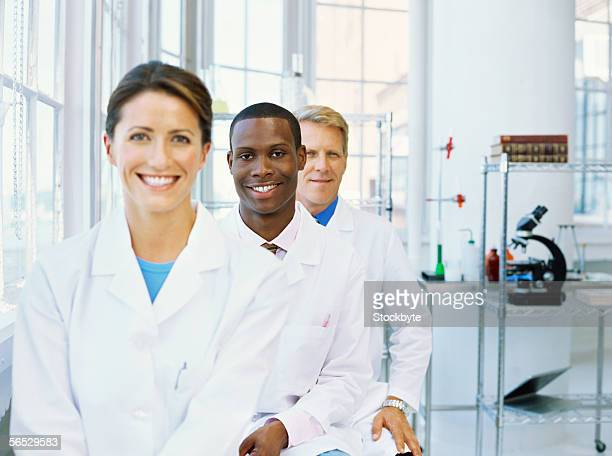 portrait of two male scientists and a female scientist standing in a row and smiling