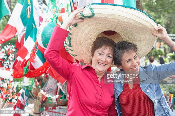 Portrait of two mature women trying on a sombrero