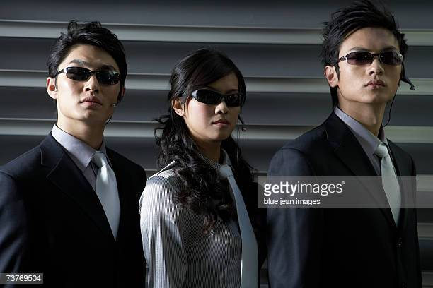 Portrait of two men and one woman in dark suits, sunglasses and headsets