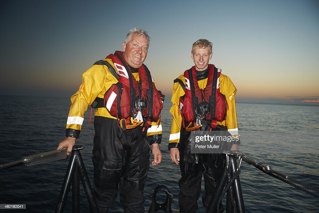 Portrait of two men crewing lifeboat at sea