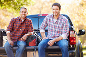 Portrait Of Two Men In Pick Up Truck On Camping Holiday Smiling To Camera
