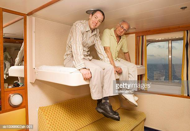 Portrait of two men sitting on bed in ferry cabin