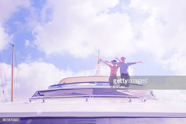 Portrait of two men with arms open, looking down from yacht