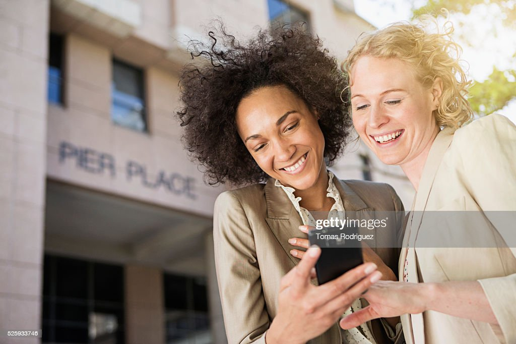 Portrait of two mid adult women using cell phone : Stock Photo
