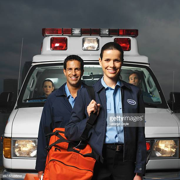 portrait of two paramedics posing in front of an ambulance