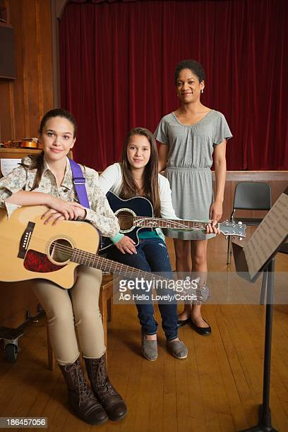 Portrait of two schoolgirls (16-17) and their teacher with acoustic guitars