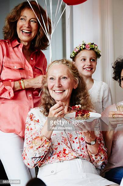 portrait of two senior woman withe a young girl at a birthday party