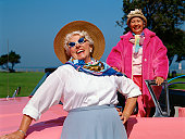 Portrait of Two Senior Women With a Pink Car in the Countryside