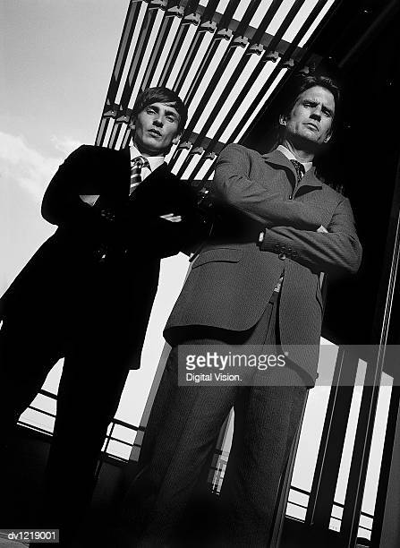Portrait of Two Serious Businessmen Wearing Full Suits Standing Side by Side