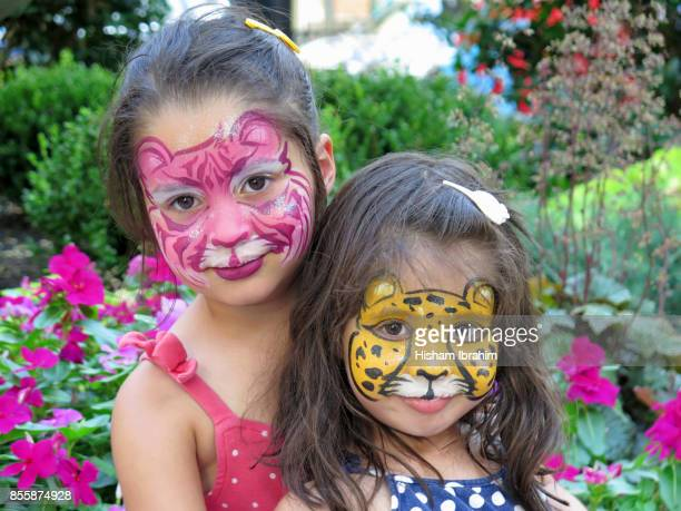 Portrait of two sisters 3 years and 5 years old with their faces painted, Washington DC, USA.