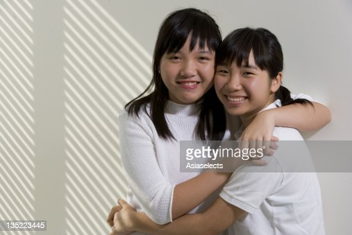 Portrait of two sisters embracing each other : Stock Photo