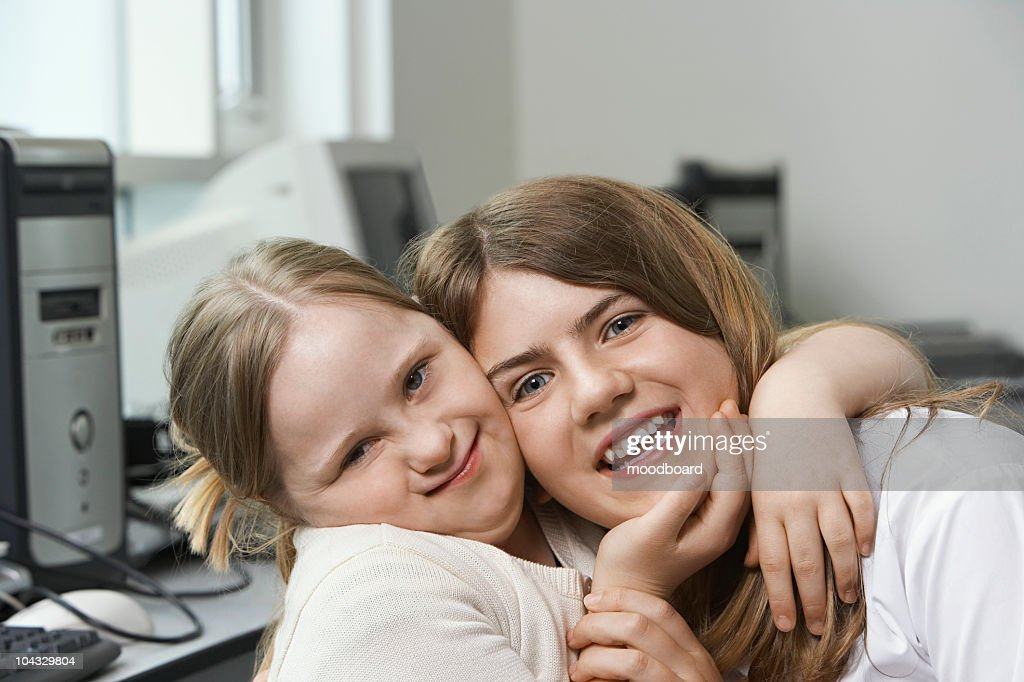Portrait of two sisters (10-15) hugging