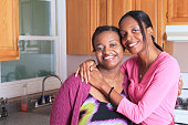 Portrait of two sisters smiling, one with learning disability