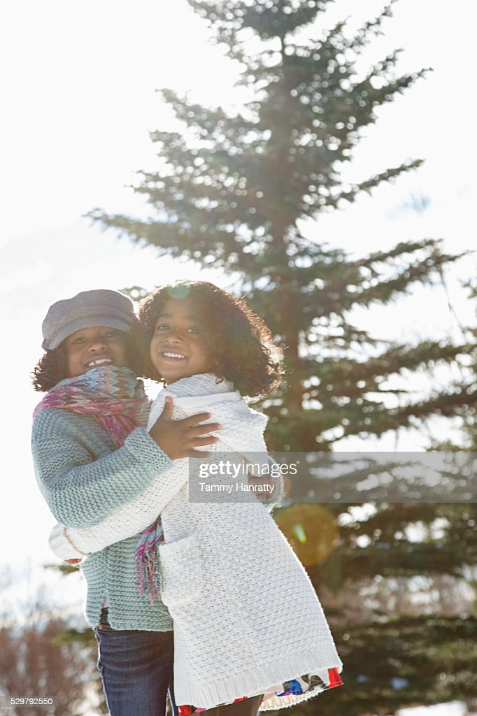 Portrait of two sisters (8-9,10-12) standing on snow : Foto de stock