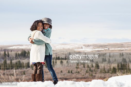 Portrait of two sisters (8-9,10-12) standing on snow : Foto stock