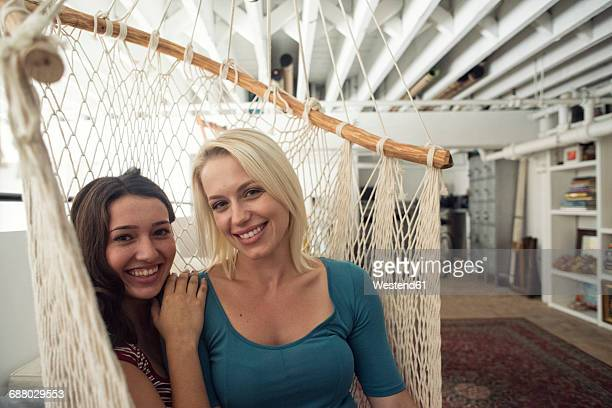 Portrait of two smiling young women in hammock