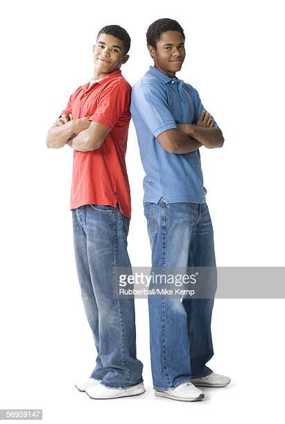 Portrait of two teenage boys standing back to back