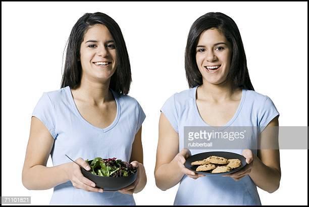 Portrait of two teenage girls holding food