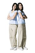 Portrait of two teenage girls standing back to back