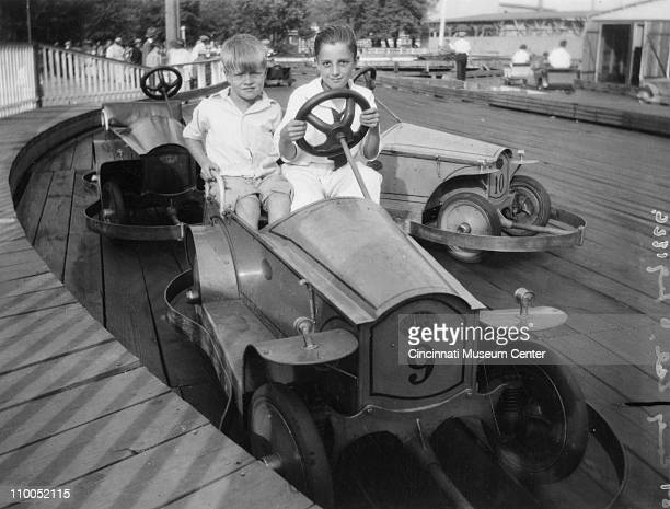 Portrait of two unidentified boys behind the wheel of a 'Custer Car' on a woodfloored track at the Coney Island amusement park Cincinnati Ohio 1926...