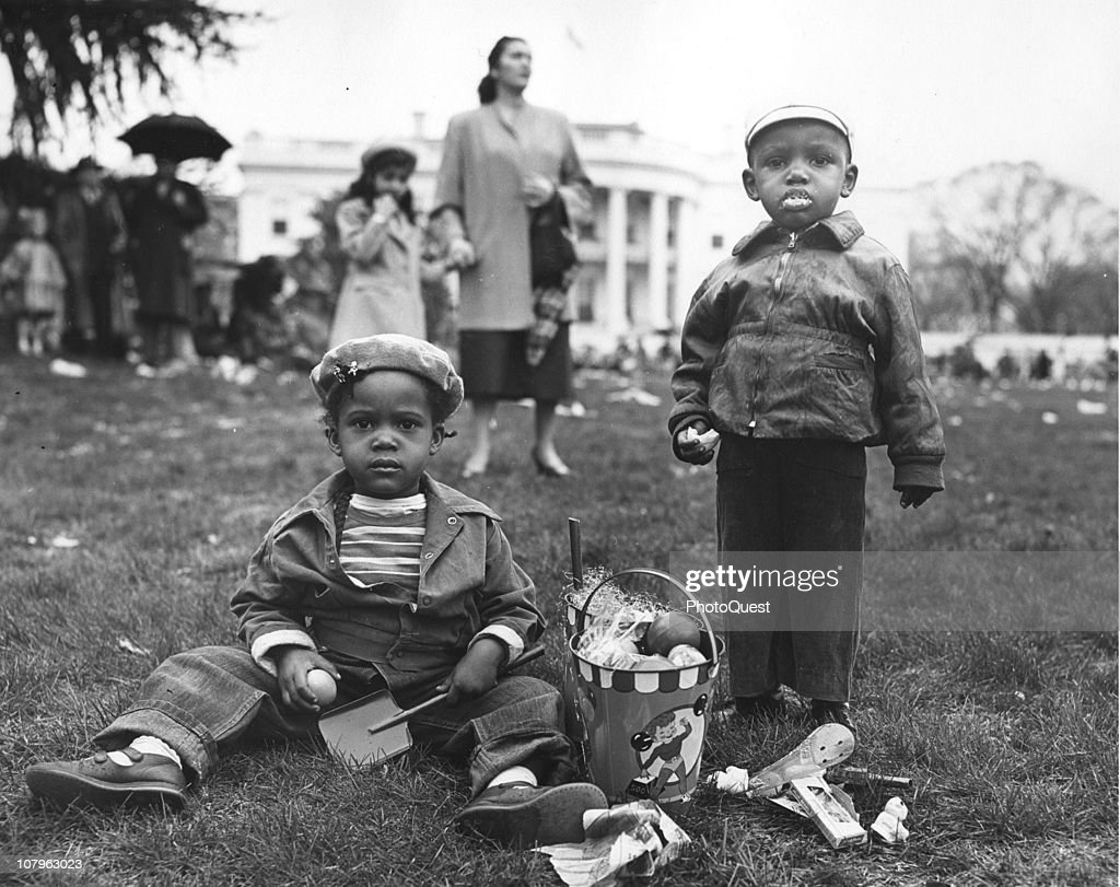 Portrait of two unidentified children on the grass at the annual White House Easter Egg Roll Washington DC April 6 1953