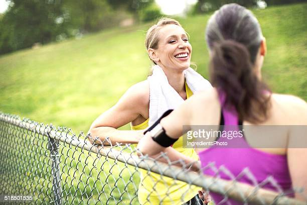 Portrait of two women talking after the workout in park.