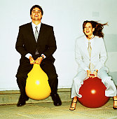 Portrait of two young executives sitting on space hoppers
