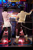 Portrait of two young girls playing in a video game arcade.