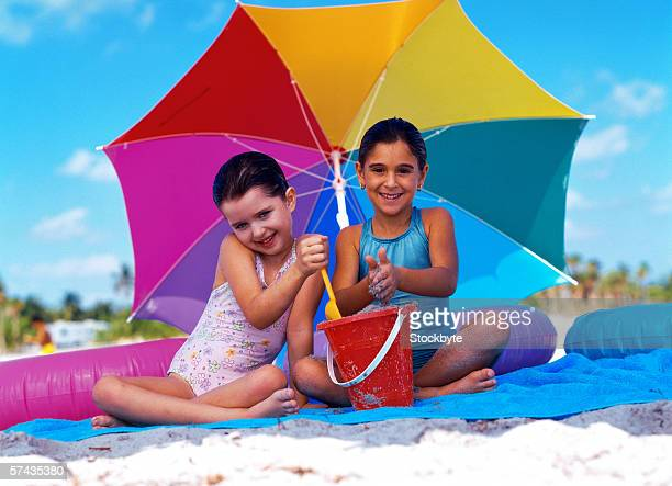 portrait of two young girls playing with sand on the beach