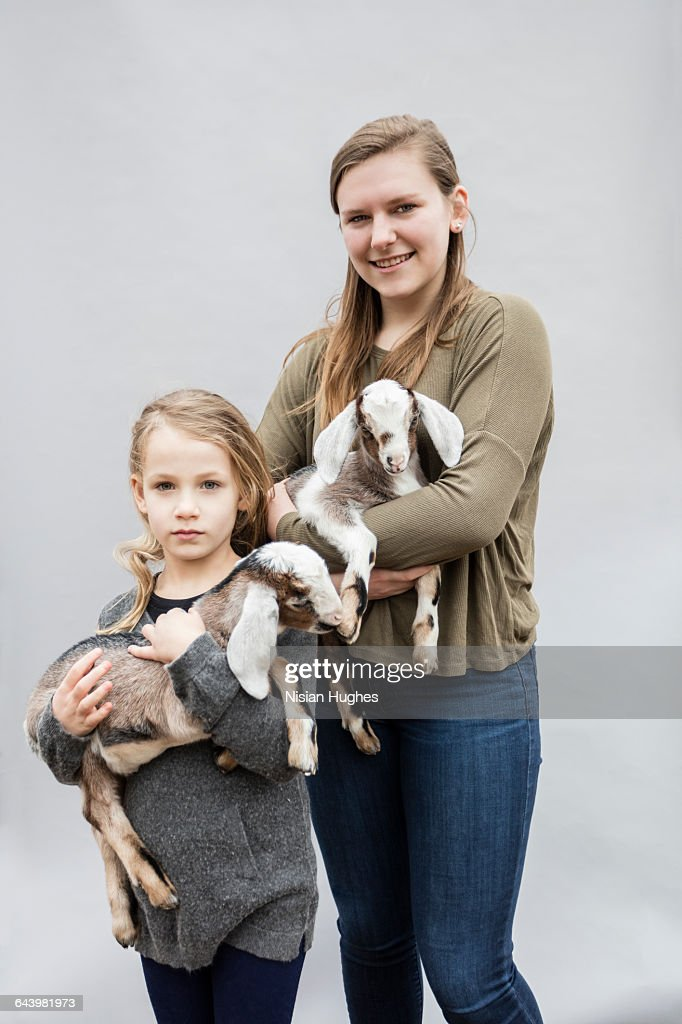 Portrait of two young girls with baby goats