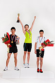 Portrait of two young men and a young woman standing on a winners podium and wearing sports medal