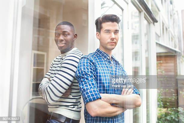 Portrait of two young men back to back in garden