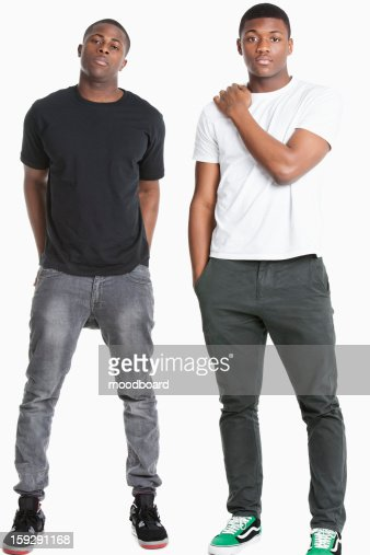 Portrait of two young men in casuals over gray background : Stock Photo