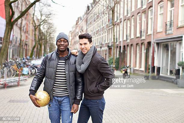 Portrait of two young men on street holding soccer ball, Amsterdam, Netherlands