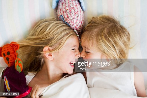 Portrait of two young sisters lying face to face in bed