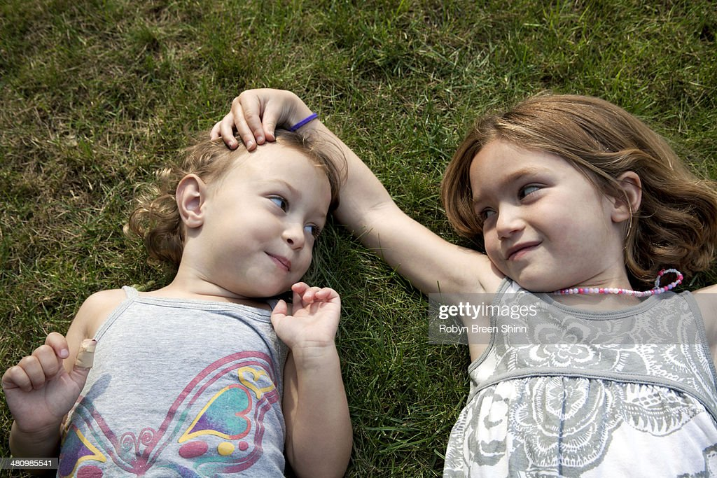 Portrait of two young sisters lying on grass